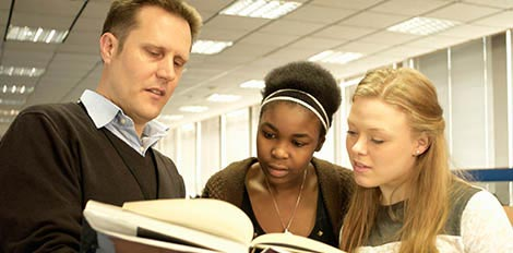 students looking at book with professor