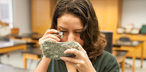 student examining rock for geology class