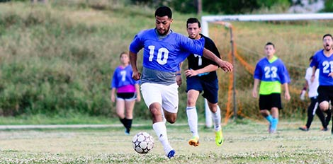 intramural soccer player dribbling the ball
