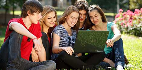 group of students outside looking at laptop