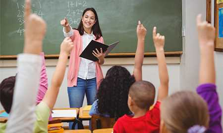 Teacher in classroom with hands raised