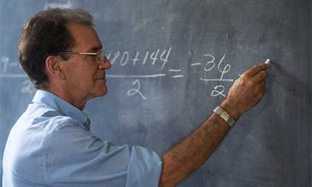 Man solving math equation on chalk board
