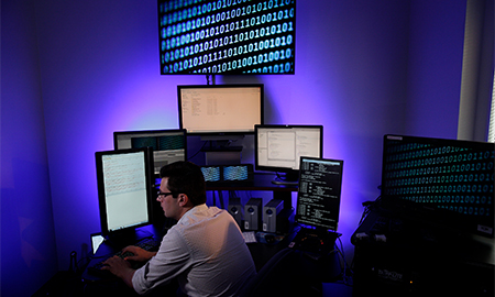 Man at desk with multiple screens