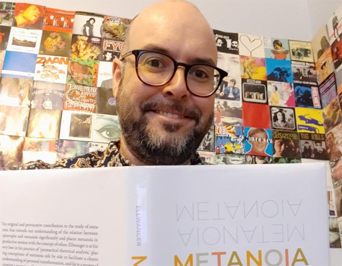 Dr. Adam Ellwanger holding his book Metanoia