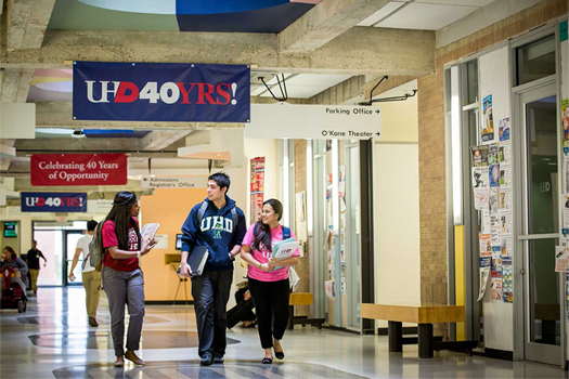 three students walking in the main hallway on the third floor of the  UHD main bulding