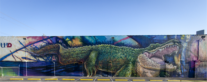 Photograph of building with alilgator painted on the side that says UHD
