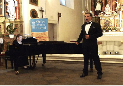 Photograph of male vocalist singing with woman at piano Orfeo Music Festival in Italy