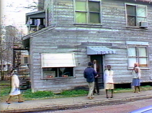 Still image from Alligator Horses film, people in front of an older wooden building.