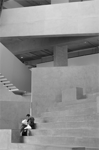 black and white photo of person sitting on steps with concrete architecture