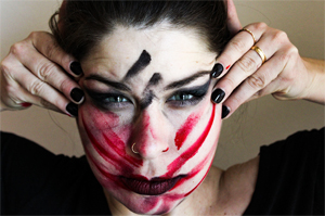 female face with smeared red and black makeup