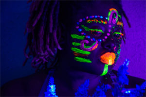 person with face painted shown in black light