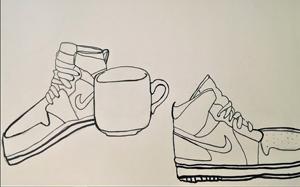 two Nike tennis shoes and a mug