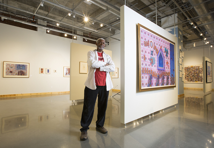 Photograph of Floyd Newsum standing in the O'Kane Gallery