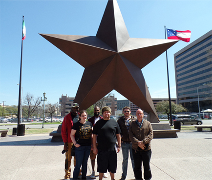 UHD students in front of a large Star statue