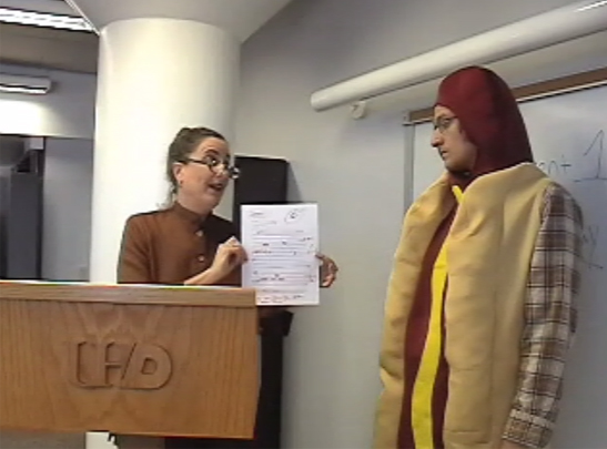 Still from video Weenies and Winners, instructor holding paper with red marks, and a man dressing in a hotdog costume