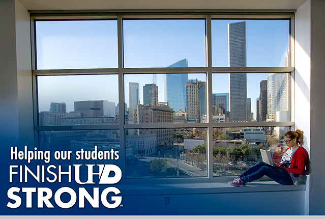 student sitting by large window overlooking Houston skyline