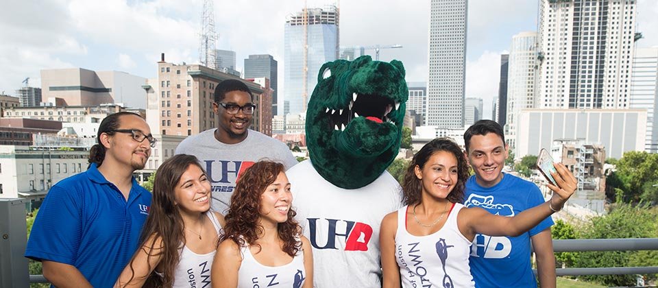 group of students ta king selfie with Ed U Gator with view of downtown skyline