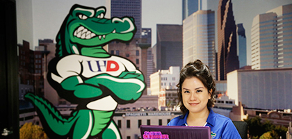 student sitting with laptop near the Ed U Gator wall decal