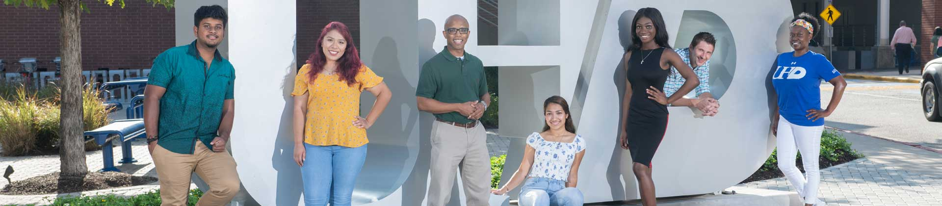 Students posing by 3 dimensional UHD sign