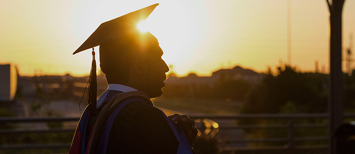 Graduating student with the sun setting in the background