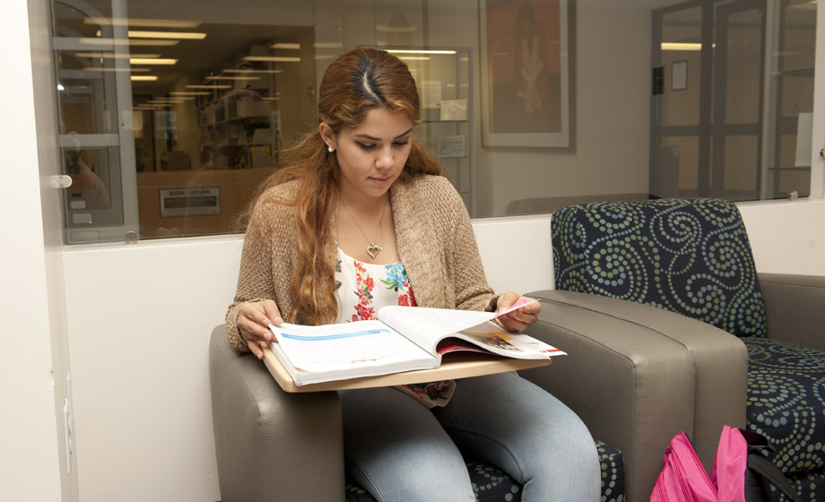 female student reading through a textbook in a reading room chair