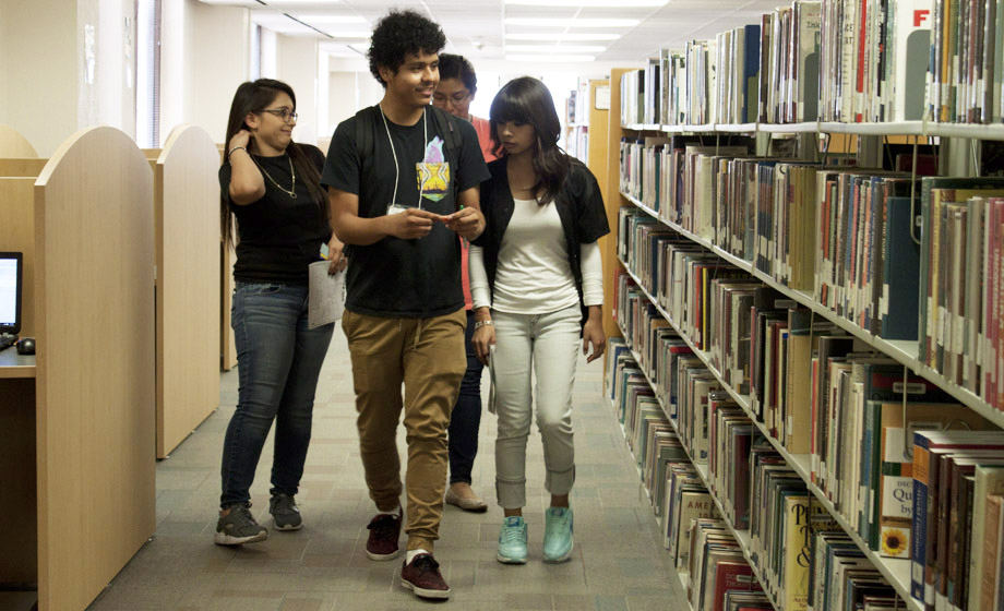 students walking in the library stacks