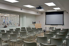 Event room with chairs lined up in rows in front of a projector and podium