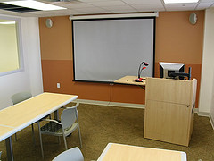 A study room with a projector, podium, and working area