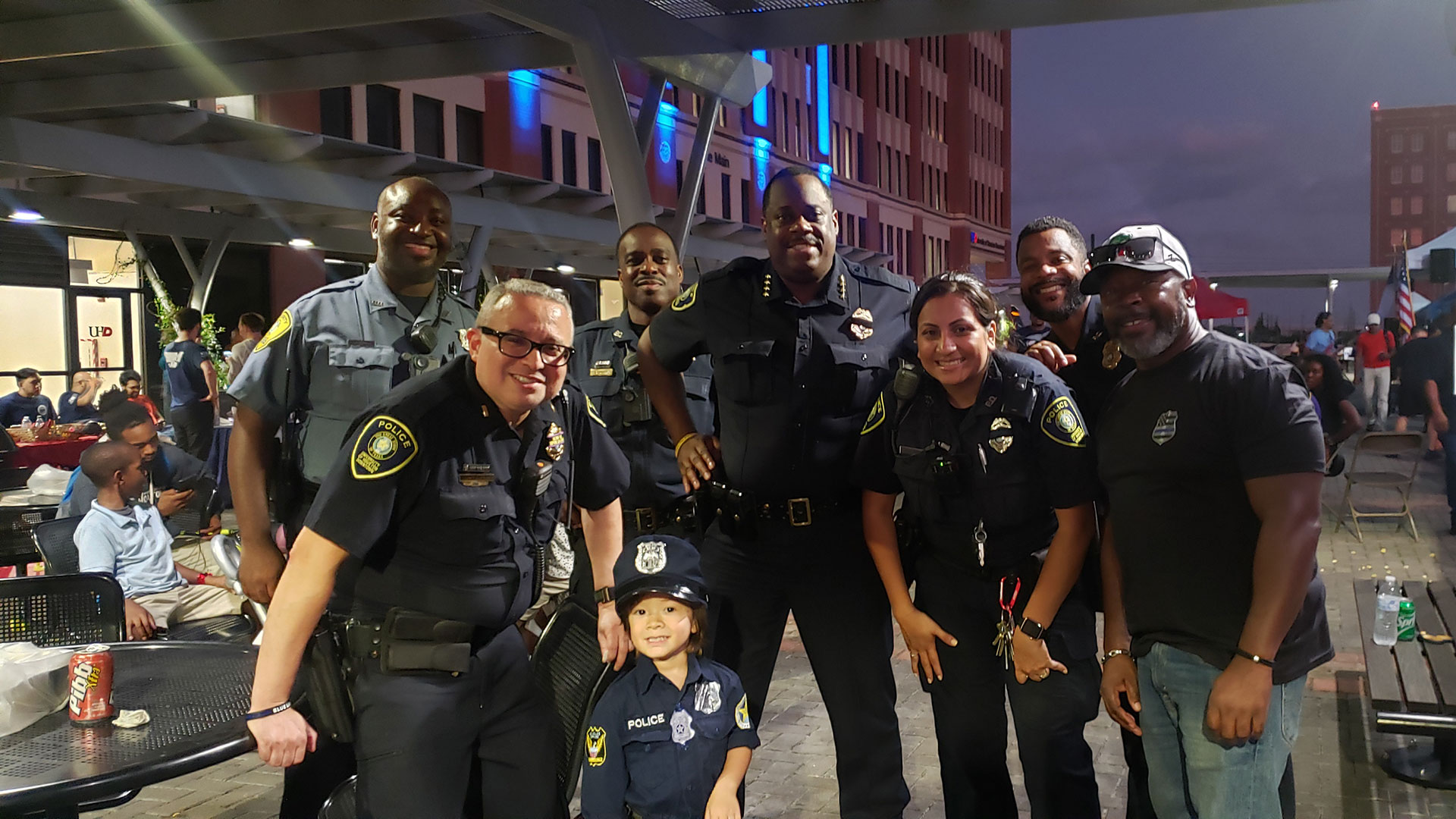 Group Photo of Police Chief and Officers with a young child dress as an officer