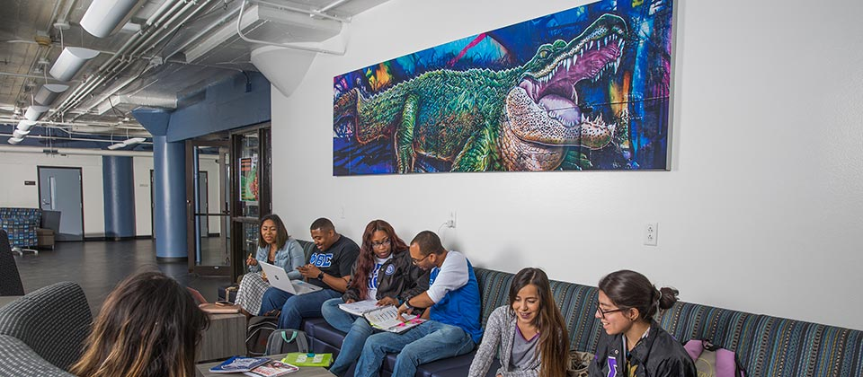 Students hanging out in a common area with a gator painting